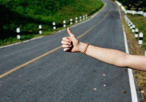 A female hand hitchhiking on a deserted road